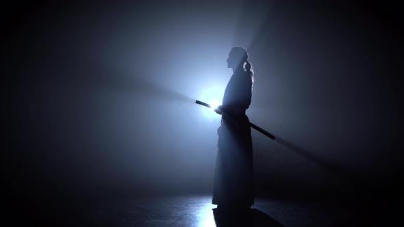 Thumbnail for Mann kämpft bei Aikido Training mit japanischem Schwert in Kampfsportschule. Gesunder Lebensstil und