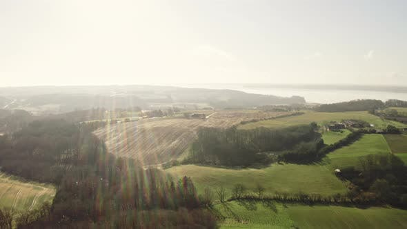 Thumbnail for Drone Over Sunlit Landscape With Lens Flare