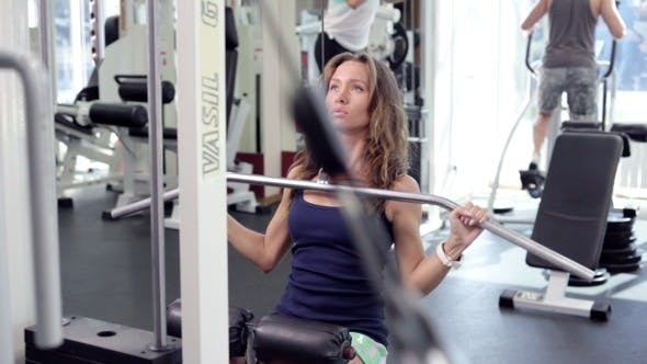 Thumbnail for Young Woman Uses Lat Machine