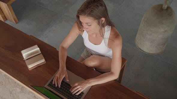 Cover Image for Caucasian Woman Working on Laptop Remotely from Tropical Patio