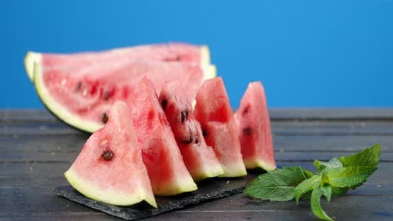 Slices of Juicy Watermelon on a Wooden Table Slowly Rotate.