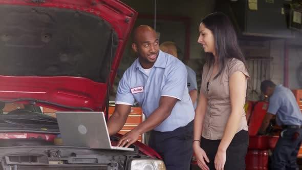 Thumbnail for Auto repairman shows customer laptop computer