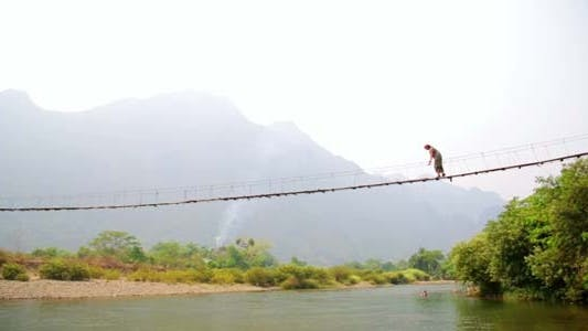 Thumbnail for Tourist Woman Crossing Bamboo Suspension Bridge, 4