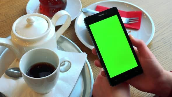 Thumbnail for A Woman Holds a Smartphone with a Green Screen Above a Table with Meal - Closeup From Above