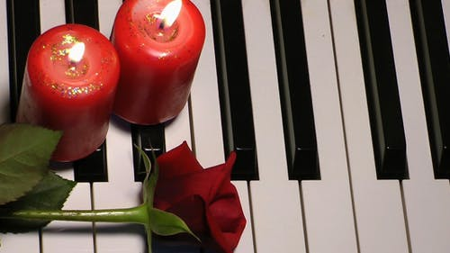 Rose and Candle on Piano Keys