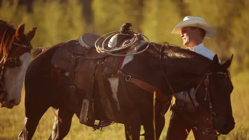 Group of cowboys saddle up and prepare for ride