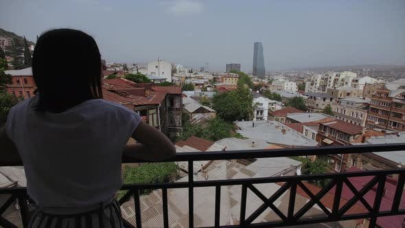 Thumbnail for Woman on Balcony with View of Old Part Tbilisi, Georgia, Roofs of Buildings, Glass Skyscrapers