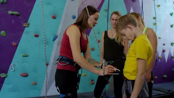 Thumbnail for Caucasian Female Climbing Coach Showing Safety Equipment for Group