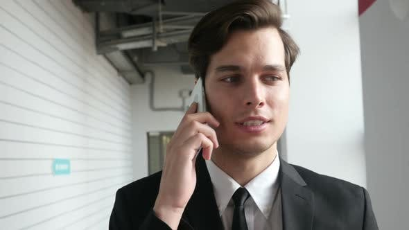 Thumbnail for Businessman Walking and Talking on Phone in Office, Close Up
