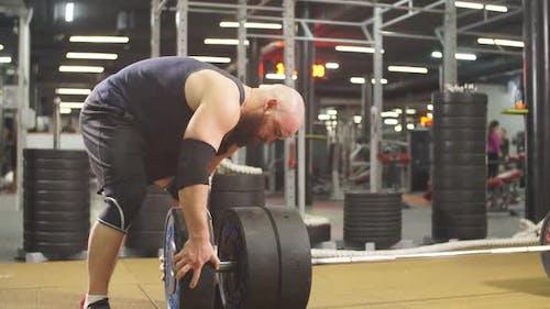 Junge männliche Powerlifter bereitet sich auf Kreuzheben der Langhantel während des Wettkampfes vor und verbringt Zeit im Fitnessstudio