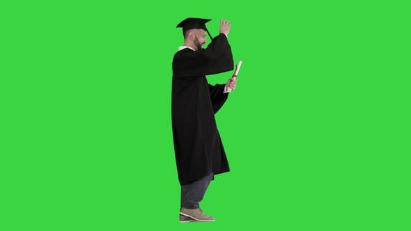 Graduate Student Walking and Tossing Up His Hat on a Green Screen Chroma Key