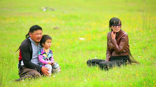 Mongolian Family Sitting On Grass