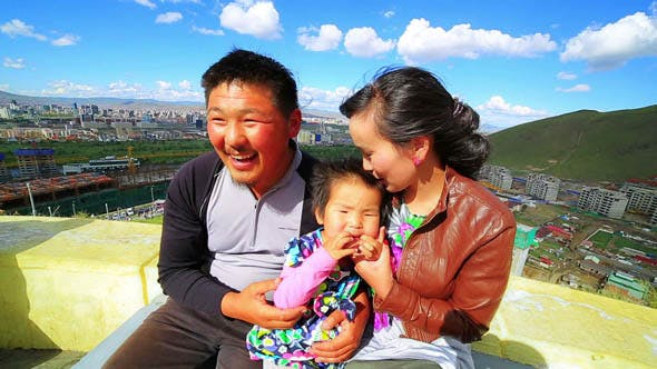 Mongolian Family, Ulaanbataar Is At Background