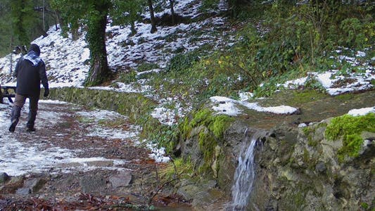 Thumbnail for Waterfall in Winter and a Man Walking in Nature