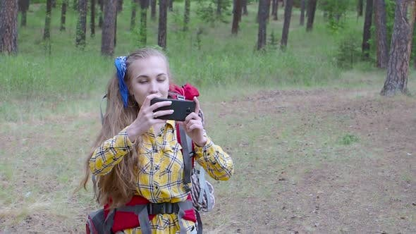 Thumbnail for Woman with Backpack Walking in a Forest and Take a Photo with a Mobile Phone.