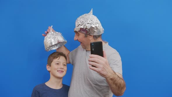 Grandfather His Grandson Protective Foil Hats From 5g Radiation Standing Blue Background
