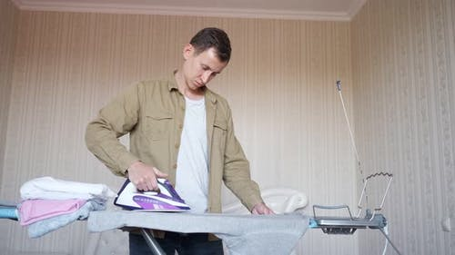 Young Man in a Shirt Ironing Things on an Ironing Board
