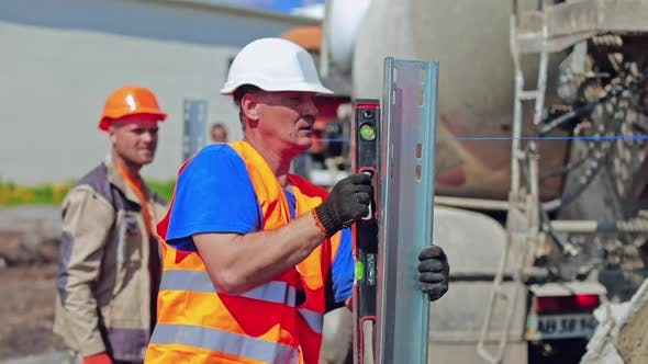 Thumbnail for Worker in safety hard hat measuring metal base outdoors