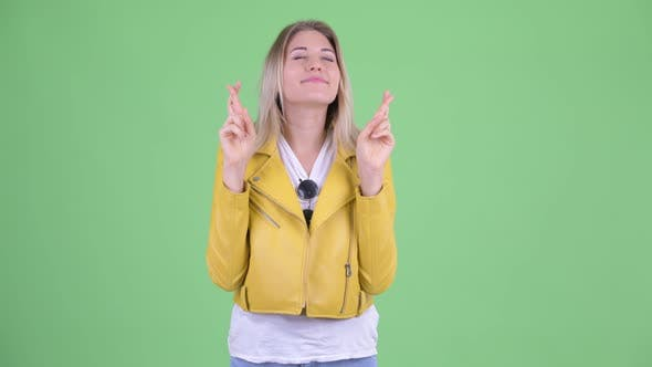 Thumbnail for Happy Young Rebellious Blonde Woman Wishing with Fingers Crossed