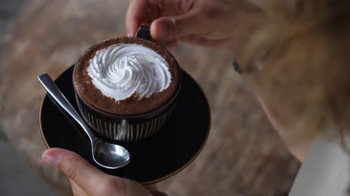Hands Taking a Cup of Dairy Free Cappuccino with Cream on Top