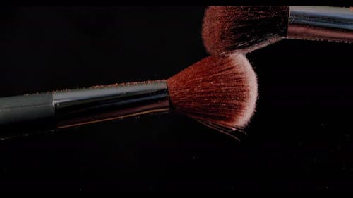Two Make-up Brush with Powder on Black Background with Sunlight Colour Paint Concept Slow Motion