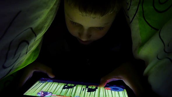 Thumbnail for Young Boy Uses A Digital Tablet Under The Covers