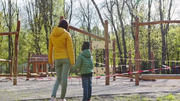 Thumbnail for a Child and Mother Near a Closed Playground