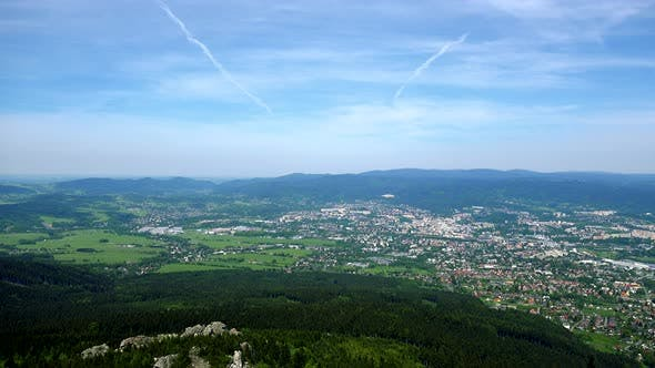 Thumbnail for A Small Town Surrounded By a Forest, the Bright Blue Sky in the Background - Top View