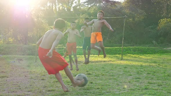 Group Of Kids Playing Soccer In Rural Area