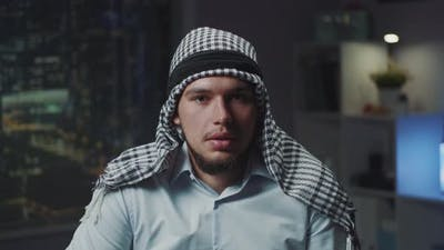 Close Up of Arab with Kandora Speaking to the Camera in Office in the Evening