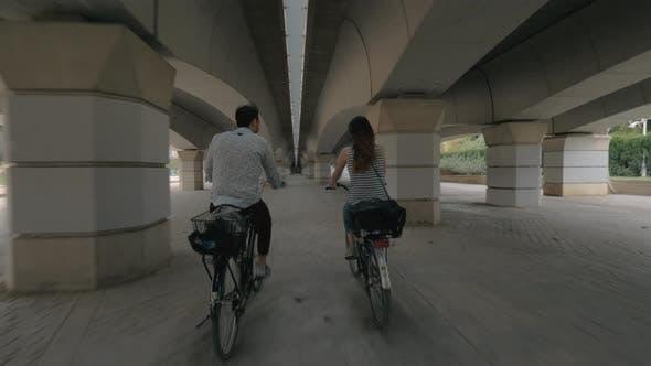 Cycling under a bridge