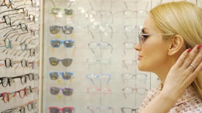 Young Woman is Choosing a Solar Glasses in Optician Store