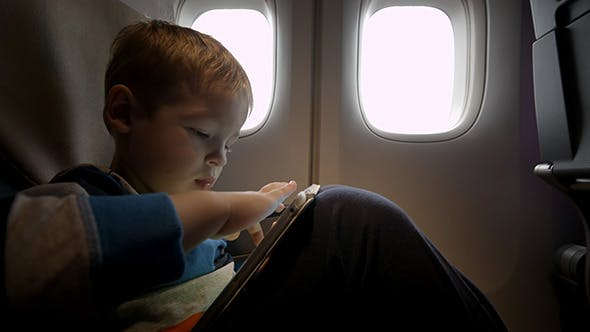 Thumbnail for Little Boy Playing On Touch Pad In The Plane