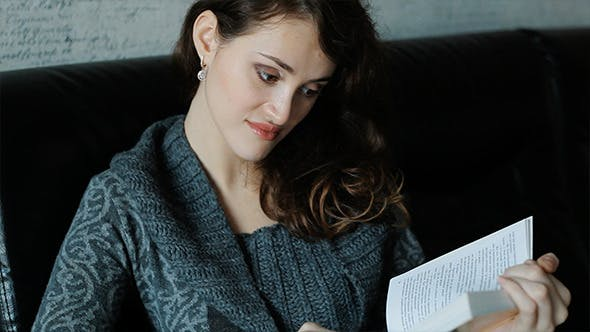 Thumbnail for Cute Young Woman Relaxing On Sofa Reading Book