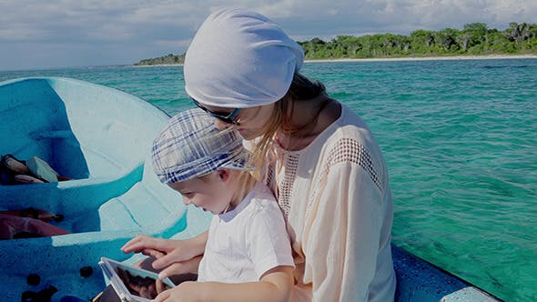 Mother And Son Using Pad While Traveling By Sea