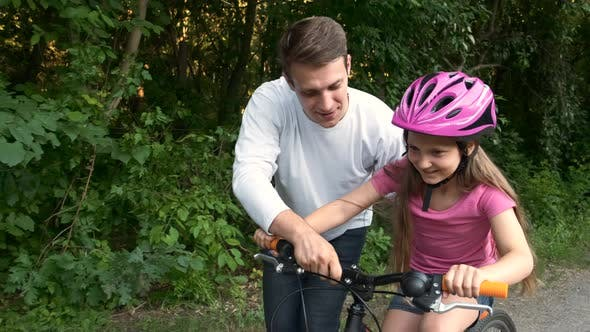 The older brother teaches the younger sister to ride a bike in the Park. The happy sport family