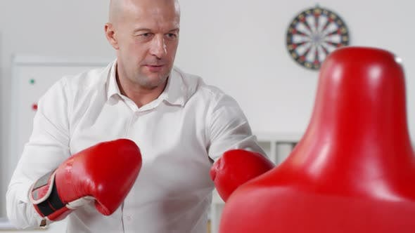 Cover Image for Middle-Aged Office Worker Punching Red Dummy