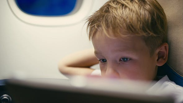 Thumbnail for Little Boy Using Tablet Computer During Flight