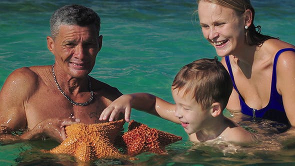 Thumbnail for Man Showing Tourists Two Big Starfish