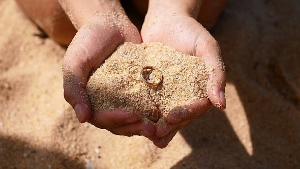 Wedding Rings in Hands with Sand