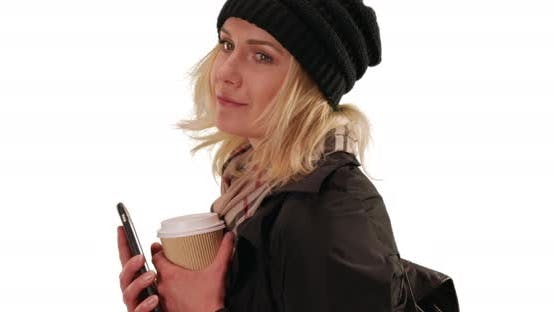 Thumbnail for White young lady in jacket and beanie using phone to text on white copy space