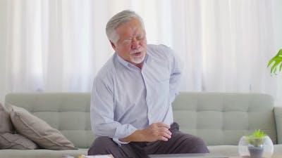 Asian Elderly senior man back pain and illness on sofa at home,Elderly Care Concept
