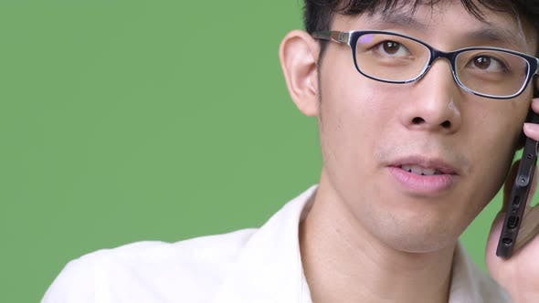 Thumbnail for Happy Young Asian Businessman Smiling While Talking on the Phone