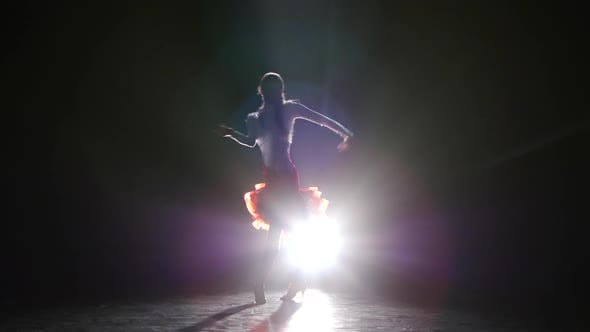 Cover Image for Beautiful Girl Dancing Latin in the Studio on a Dark Background, Smoke, Silhouette