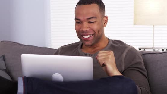Thumbnail for Black man watching the game on his laptop