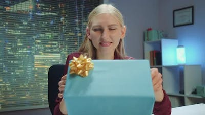 Happy Young Woman Presenting Gift to the Camera and Smiling