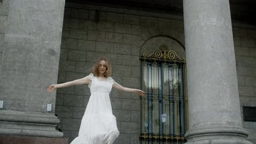 Young Dancer in White Dress Dances on the Stairs of the Theatre in Slow Motion Balerina Does Dance