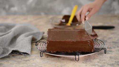 Der Konditorei glasiert einen Kuchen.