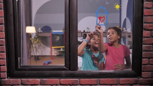 Happy Mixed Race Sisters Painting on Window Pane