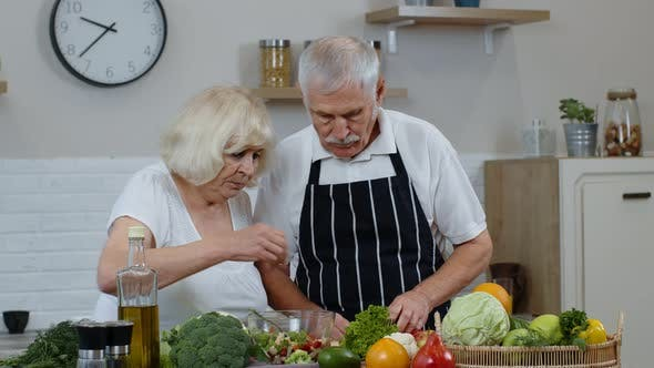 Thumbnail for Senior Grandparents in Kitchen Interior. Senior Woman and Man Cooking Salad with Fresh Vegetables
